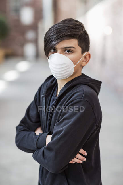 Pre-teen boy standing wearing a protective mask to protect against COVID-19 during the Coronavirus World Pandemic; Toronto, Ontario, Canada — Stock Photo