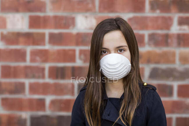 Young girl standing wearing a protective mask to protect against COVID-19 during the Coronavirus World Pandemic; Toronto, Ontario, Canada — Stock Photo