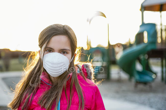 Jeune fille debout sur une aire de jeux portant un masque de protection contre la COVID-19 pendant la pandémie mondiale de coronavirus ; Toronto, Ontario, Canada — Photo de stock