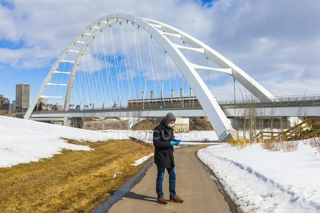 Man wearing a mask and gloves standing on a path outside using his smart phone during the Covid-19 world pandemic; Edmonton, Alberta, Canada — Stock Photo