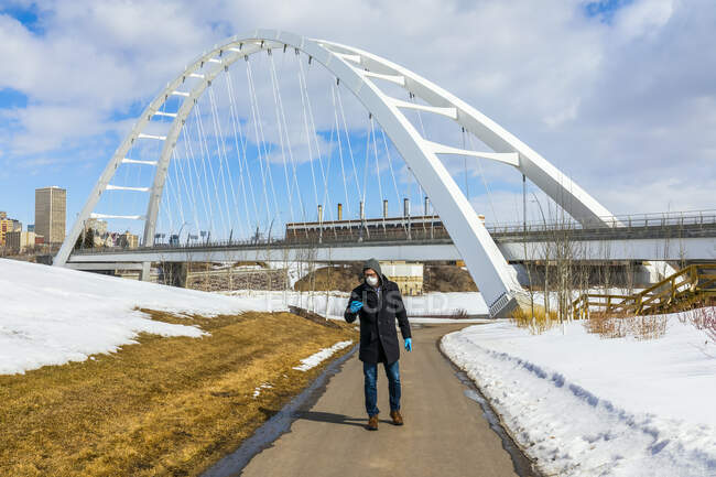 Man wearing a mask and gloves walking on a path outside using his smart phone during the Covid-19 world pandemic; Edmonton, Alberta, Canada — Stock Photo