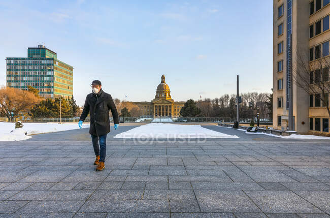 Man wearing a mask and gloves walking on a path by the Legislature during the Covid-19 world pandemic; Edmonton, Alberta, Canada — Stock Photo