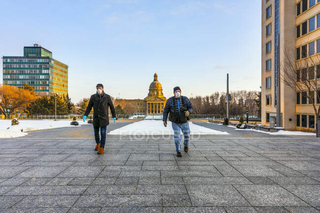 Men wearing masks and gloves walking on a path by the Legislature during the Covid-19 world pandemic; Edmonton, Alberta, Canada — Stock Photo