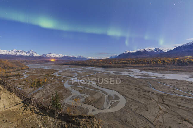 Northern Lights Above Braided Matanuska River Bed With Mountains And City Light In Background, Fall, Southcentral Alaska, USA — Stock Photo