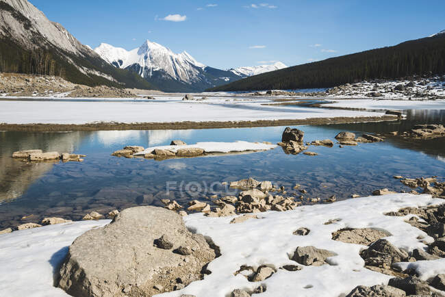 Snow on the lake and snow-capped rugged mountains peaks in Jasper National Park; Alberta, Canada — Stock Photo