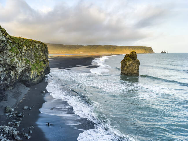 Cliffs and a rock formation along the coastline of the Southern Region of Iceland, with the surf washing up onto black sand in the foreground; Myrdalshreppur, Southern Region, Iceland — Stock Photo