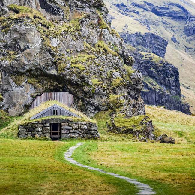 Barn built into a rocky mountainside, now overgrown with grass; Rangarping eystra, Southern Region, Iceland — Stock Photo