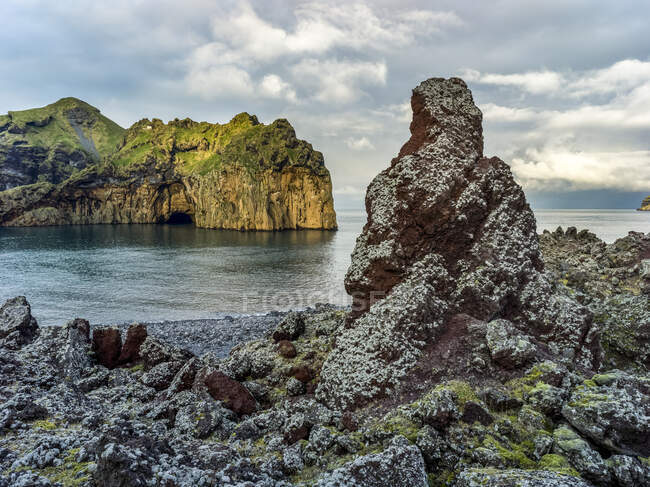 Rugged rock and cliffs along the coast of the island of Heimaey, a part of an archipelago along the Southern coast of Iceland; Vestmannaeyjar, Southern Region, Iceland - foto de stock