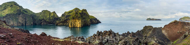 Rugged rock and cliffs along the coastline of the island of Heimaey, a part of an archipelago along the Southern coast of Iceland; Vestmannaeyjar, Southern Region, Iceland — Stock Photo