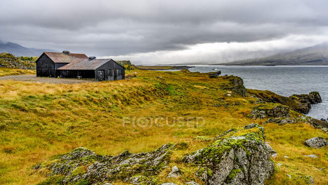 A house facing the water along the coastline of fjord Berufjorour; Djupivogur, Eastern Region, Iceland — Stock Photo