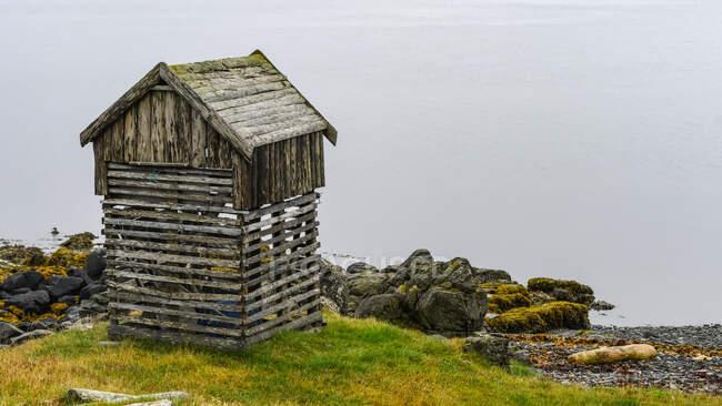 Estructura de madera en el borde del Steingrimsfjorour, en Drangsnes, una pequeña ciudad en la parte occidental de Islandia; Islandia - foto de stock