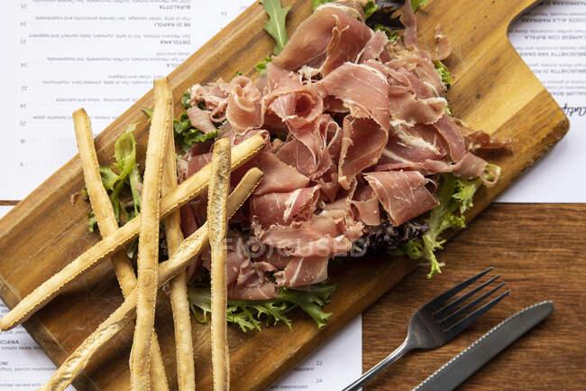 Prosciutto and grissini on wooden board; Melbourne, Victoria, Australia — Stock Photo
