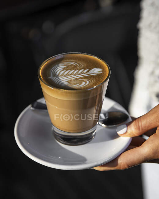Cafe Latte with coffee art design being held by female hand; Melbourne, Victoria, Australia — Stock Photo