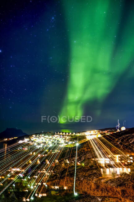 Northern Lights over an illuminated city in Greenland; Greenland — Foto stock