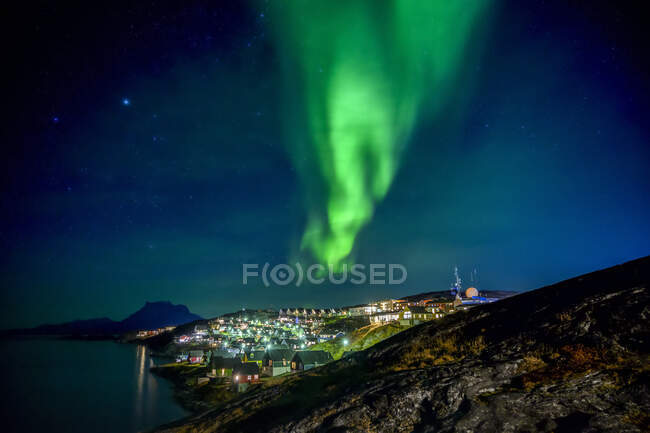 Northern Lights over the glowing city of Nuuk; Nuuk, Sermersooq, Greenland — Foto stock