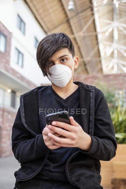 Garçon utilisant son téléphone intelligent et portant un masque de protection contre la COVID-19 pendant la pandémie mondiale de coronavirus ; Toronto, Ontario, Canada — Photo de stock