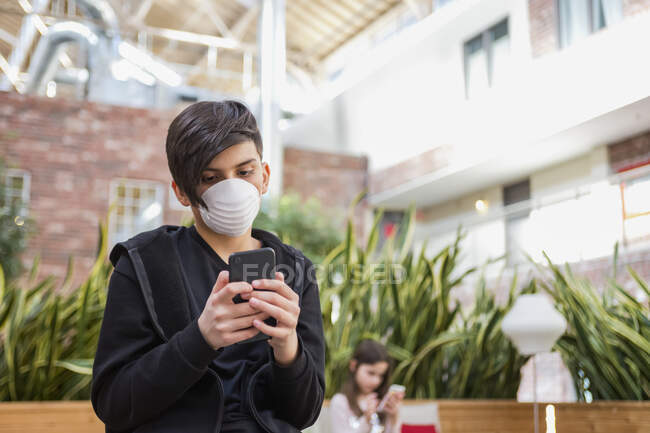 Boy with smart phone wearing protective mask to protect against COVID-19 during the Coronavirus World Pandemic, and his younger sister in the background; Toronto, Ontario, Canada — Stock Photo