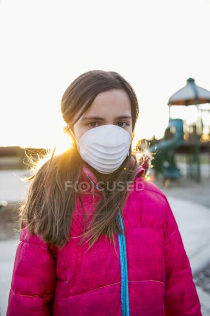 Junges Mädchen mit Schutzmaske zum Schutz vor COVID-19 während der weltweiten Coronavirus-Pandemie auf einem Spielplatz; Toronto, Ontario, Kanada — Stockfoto