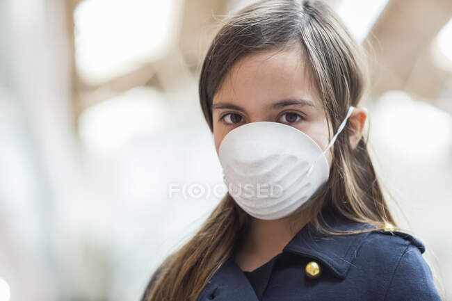 Jeune fille debout portant un masque de protection contre la COVID-19 pendant la pandémie mondiale de coronavirus ; Toronto, Ontario, Canada — Photo de stock