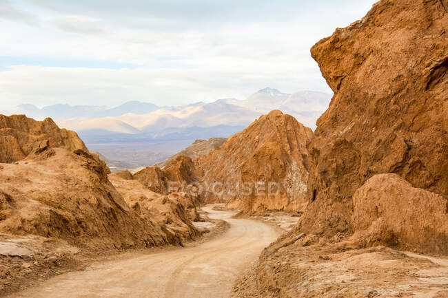 Dirt road winding through a colourful canyon in the high Andes; San Pedro de Atacama, Atacama, Chile — Stock Photo
