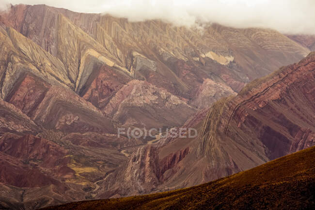 Geologically interesting mountain is lit in reddish tones by the stormy late day sun; Humahuaca, Jujuy, Argentina — Stock Photo