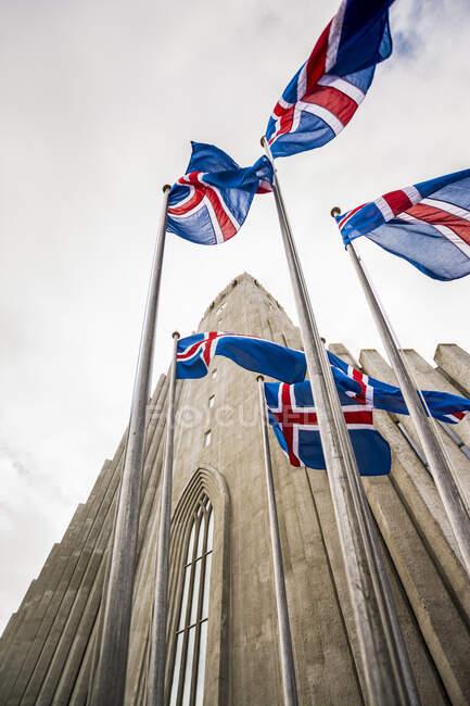 Weitwinkel einer grauen Betonkirche, Hallgrimskirkja und isländische Flaggen; Reykjavik, Reykjavik, Island — Stockfoto