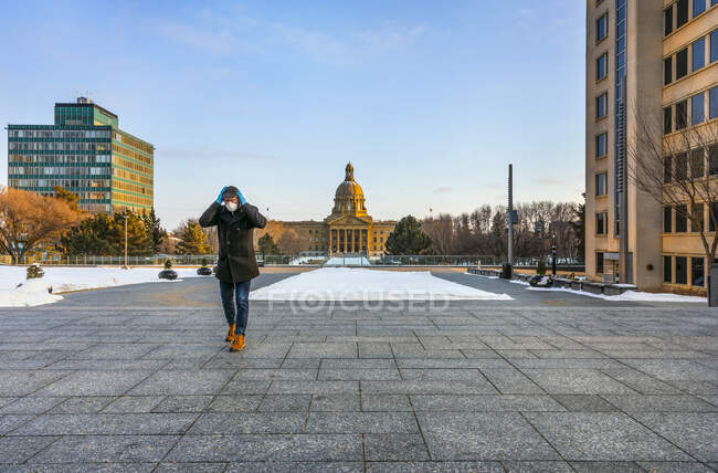Man wearing a mask and gloves holding his hands on his head as he walking on a path by the Legislature during the Covid-19 world pandemic; Edmonton, Alberta, Canada — Stock Photo