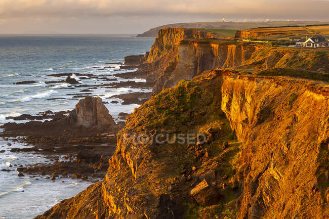 Dramatic rocky cliffs along the shoreline with the orange glow of sunset; Cornwall County, England — Stock Photo