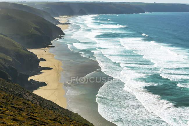 Песчаные пляжи с серфингом вдоль короткой линии скал с голубым небом и облаками; графство Корнуолл, Англия — стоковое фото