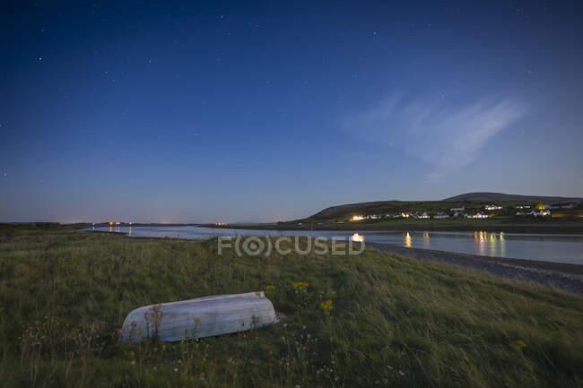 Маленькая белая лодка по реке с маленькой деревней на противоположном берегу реки, снятая ночью со звездами в небе; Огиниш, графство Клэр, Ирландия — стоковое фото