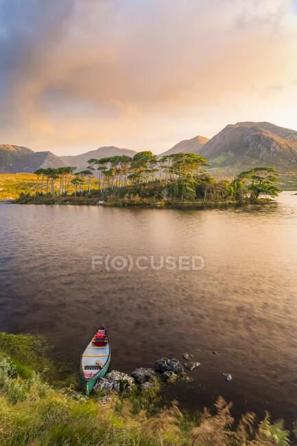 Каноэ на берегу озера, указывающее на остров с соснами и эпическим восходом солнца на заднем плане; Коннемара, графство Голуэй, Ирландия — стоковое фото
