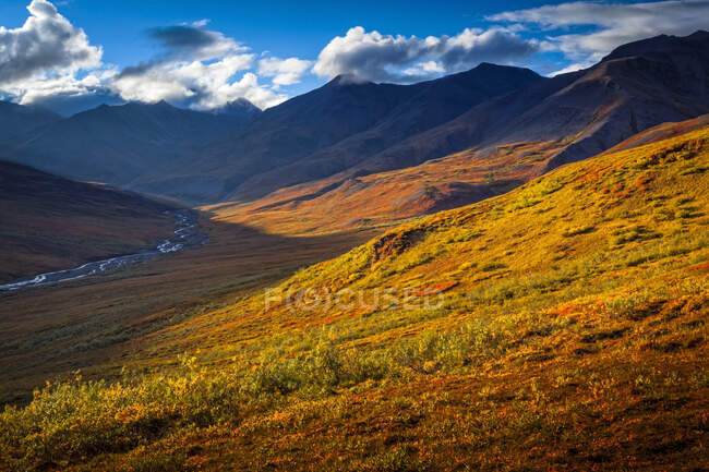 Brooks Mountains and Kuyuktuvuk Creek Valley in fall colours under blue sky. Gates of the Arctic National Park and Preserve, Arctic Alaska in autumn; Alaska, United States of America — Stock Photo