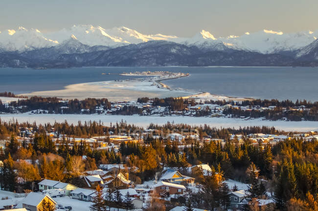 Aerial view of the city of Homer and the Homer Spit in Kenai Peninsula Borough, in Kachemak Bay in winter with the Kenai Mountain Range in the distance; Kenai Peninsula, Alaska, United States of America — Stock Photo