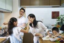 Feliz família asiática preparando comida juntos em casa — Fotografia de Stock