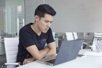 Красивый Азии бизнесмен, работы с ноутбуком в офисе — стоковое фото