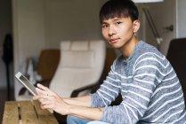 Junger Mann blickt mit Tablet in der Hand in die Kamera — Stockfoto