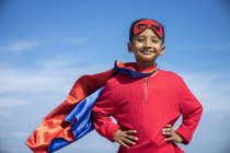 Criança super-herói contra fundo céu azul . — Fotografia de Stock