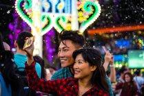 Feliz asiático casal passar tempo juntos no parque de diversões no Natal e tomando selfie — Fotografia de Stock