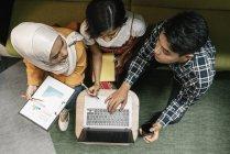 Vista superior de gente de negocios multicultural jóvenes trabajando con el portátil en la oficina moderna - foto de stock