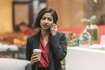 Молодая азиатская деловая женщина разговаривает по мобильному телефону в современном офисе — стоковое фото