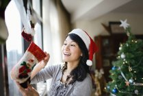 Asian family celebrating Christmas holiday, woman decorating house — Stock Photo