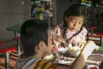 Двое счастливых молодых людей с детьми едят в кафе — стоковое фото