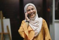 Mujer de negocios asiática joven en hijab con smartphone en oficina moderna - foto de stock