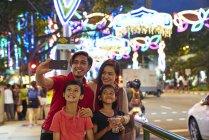 Família alegre tirando selfies no Hari Raya Geylang Bazaar, Cingapura — Fotografia de Stock
