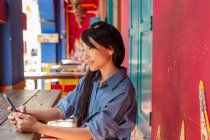 Attractive adult asian woman using smartphone — Stock Photo