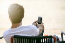 Joven sentado afuera en una playa y mirando a lo lejos con un smartphone en la mano - foto de stock
