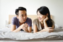 Mature asian casual couple lying in bed — Stock Photo