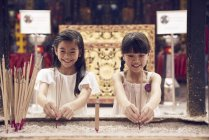 Two young asian girls placing candles at shrine — Stock Photo