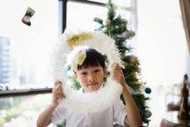 Азиатская семья празднует Рождество праздник, мальчик с рождественским венком — стоковое фото