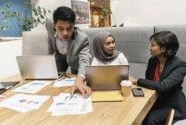 Jóvenes empresarios multiculturales que trabajan con dispositivos digitales en oficinas modernas - foto de stock